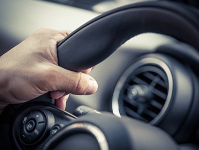close up of hands on teh steering wheel of a quality used car